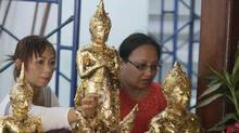 Thai Buddhists apply pieces of gold to Buddha statues for good luck at Wat Phra Chetuphon temple in Bangkok on Jan. 9, 2012. (Sakchai Lalit/Sakchai Lalit/Associated Press)