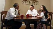 U.S. President Barack Obama meets with Jason and Ali McLaughlin and their son Cooper in the dining room of their home in Cedar Rapids, Iowa, July 10, 2012. (JASON REED/REUTERS)