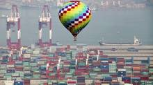 A hot-air balloon flies over a container port in Qingdao in east China's Shandong province on Sunday, Sept. 9, 2012, during a meeting of Asia-Pacific leaders. (Associated Press)