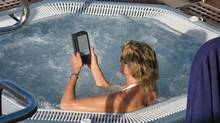A woman uses an Amazon Kindle e-reader in a whirlpool on board a cruiseshiip. (Randall Moore/The Globe and Mail)