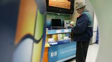 In this file photo a shopper, viewed through an ad display for Microsoft Corp.'s Windows Vista computer operating system, looks at a box containing the software Tuesday, Jan. 30, 2007 at a CompUSA store in Mountlake Terrace, Wash., north of Seattle. (Ted S. Warren/Ted S. Warren/AP)