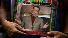 A supporter of President Hugo Chavez holds a picture of him decorated with a rosary and the words in Spanish 'Merry Christmas' outside the National Assembly in Caracas, Venezuela, on Jan. 5, 2013. (Fernando Llano/Associated Press)