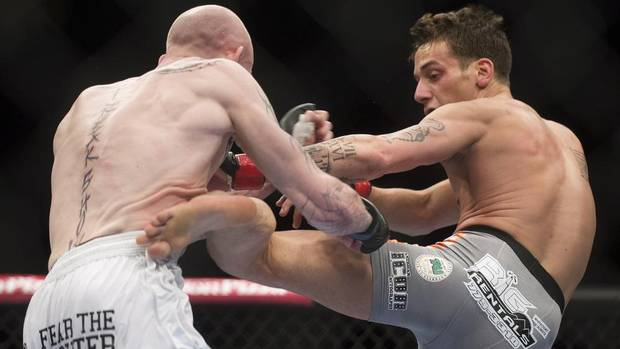 Mike Ricci, right, from Canada, lands a kick to the body of Colin Fletcher, from England, during their UFC 158 lightweight fight in Montreal, Saturday, March 16, 2013. (Graham Hughes/THE CANADIAN PRESS)